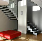 A landing staircase runs around a free wall in a room with laminate floor, hanging lamp and red leather sofa.