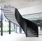 A steel winding staircase with concrete treads in an office, in front of the glass wall of a conference room and on an office garden.
