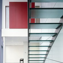 A glass staircase in a high room with a red filing cabinet and black chairs.