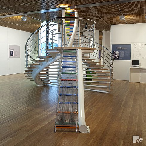 A work of art with a DNA strand and a slide in an exposition space with acoustic ceiling.