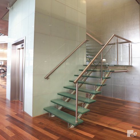 A staircase with glass treads and a platform for a lift shaft with lift door on a wooden parquet floor.