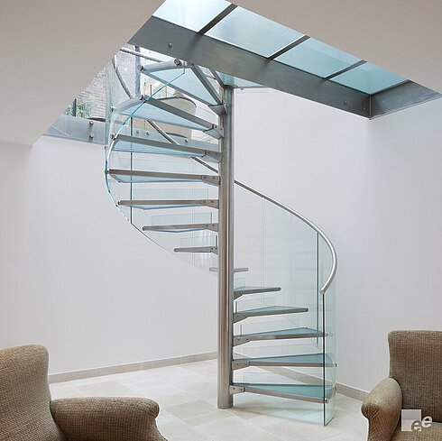 White stuccoed walls with two armchairs, a spiral staircase with stainless steel spindle, stainless steel handrails, glass steps and glass railings.