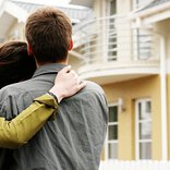 A woman embraces a man and looks with him at a house with a balcony.