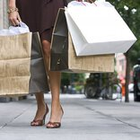 A stoop walked by a woman in shoes with spike heels, while she carries three shopping bags.