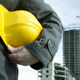 Someone in work clothing holds onto a yellow construction helmet, with two buildings under construction in the background.