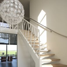 A hanging lamp from IKEA in the shape of a bird's nest next to a staircase with balustrade system and chairs further up.