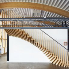 A bamboo staircase in a property with wooden rafters and a curved corrugated roof with air conditioning.