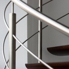 A stainless steel balustrade with  mid-rails on floating wooden treads and in front of a stucco wall.