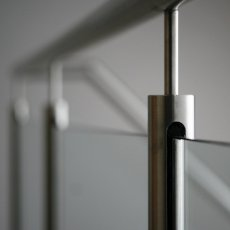 A blurry photo of a glass balustrade, but focused on one of the stainless steel balusters.