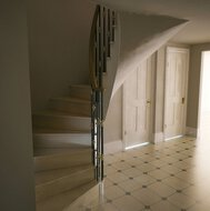 A winding staircase with treads of Crema Marfil marble, a natural stone floor and panel doors in a residence in London.