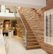 A floating staircase with wooden treads in a shop with sunglasses and a wall with a depicted face.