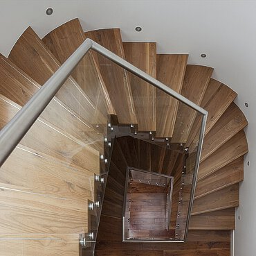 Dark walnut wood staircase treads, wall lighting and a glass balustrade in a residence in Westminster in London.