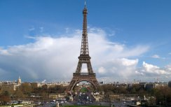 View of the Eiffel Tower in Paris, with a blue sky and a large cloud as the background.