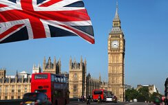 Big Ben and the Palace of Westminster in London, a red double-decker and the British flag.