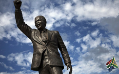 A statue of Nelson Mandela, with balled fist under cloud cover. The flag of South Africa is behind it.