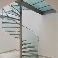 A stainless steel spiral staircase with floating and glass treads, on a natural stone floor under a glass canopy.