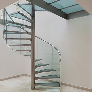 A spiral staircase under a glass floor on a natural stone floor, in a residence on the Thames.