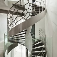 A spiral staircase with walnut wood treads and white powder-coated balustrade with cell motif in an apartment in Le Havre.