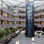 Atrium with several floors, black floor tiles on the ground and a glass roof.