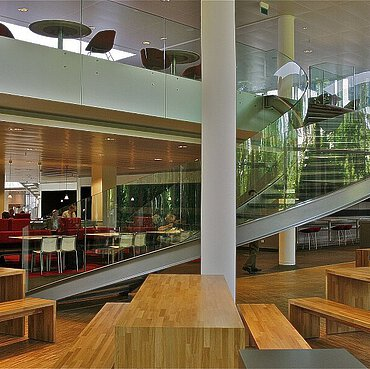 A spiral staircase with glass railings, wooden benches, tables and floor in a canteen.