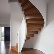 A winding staircase with oaken treads, a parquet floor, a door and stucco work in a living room in Berkshire.