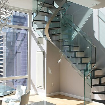 A staircase in a penthouse, with a window frame, parquet floor, table and chairs and a hanging lamp.