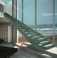 A flight of stairs in a holiday residence with glass façade, a cabinet and a view of the Atlantic Ocean.