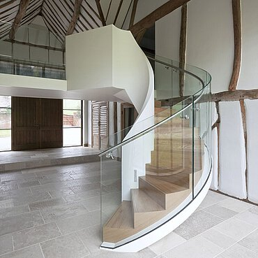 A winding staircase with balustrade in a shed with wooden beams, wooden double doors and natural stone floor.