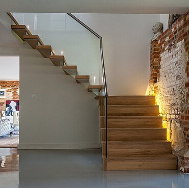 An oaken landing staircase by a brick wall, above a peek-through on a living room with a chair in it.