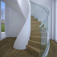 A winding staircase with wooden treads in a space with laminate floor and view of a meadow and trees.