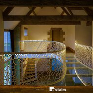 Balustrades with cell motif on a roof level with wooden floor and wooden beams, glass floor plates and a door.