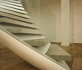 A winding staircase with marble treads and EeSoffit finish, above a laminate floor and in front of a pillar.