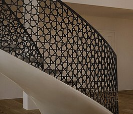 A winding staircase of EeSoffit material and a balustrade with motif, on a parquet floor and by a pillar.
