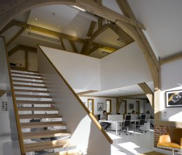 An open staircase in a studio with wooden beams, chairs and a partly brick wall in Buckinghamshire.