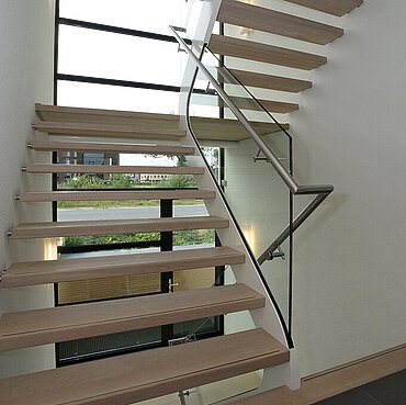 A platform staircase in a stairwell, with a glass façade with view of a road and vegetation behind it.
