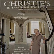 The cover of Christie's International Real Estate Magazine shows a woman by a staircase in a hall.