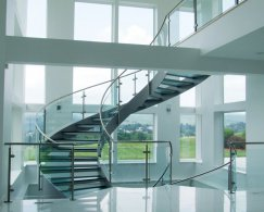A winding staircase with glass treads in a residence in Orwigsburg in Pennsylvania, with a view of a valley.