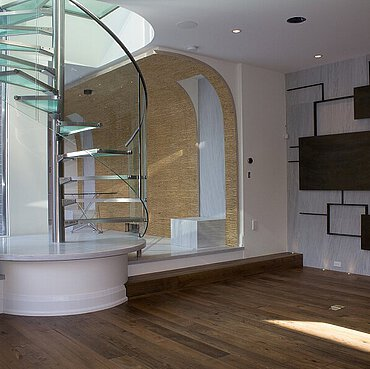 A spiral staircase with frosted glass treads and glass balustrade, on a laminate floor in a residence in Canada.