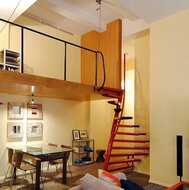 An apartment containing a table and chairs, paintings, a wooden loft and a 1m2 staircase.