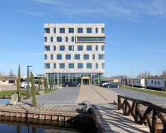 Exterior and surroundings of the building of the tax consultancy bureau LIMES, parking lot with cars and a bridge over water.