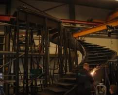 Construction of a spiral staircase in the workplace, an employe is welding, a roller door, welding machine and crane are in the background.