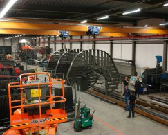 Overview of the workshop where a staircase is moved for transport by two cranes, concrete floor, fluorescent lighting.