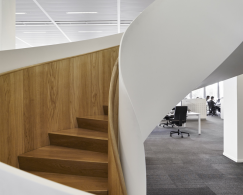 A spiral staircase with solid oak wooden steps in an office environment with carpet tiles on the floor.