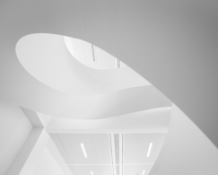 The bottom of a white spiral staircase to which EeSoffit has been applied, fluorescent lighting in the background