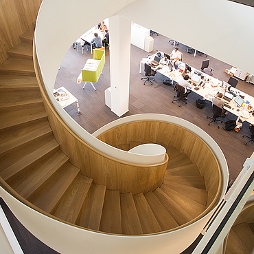 Top view of a spiral staircase, adjacent to work stations with office chairs and computers and a waiting area.