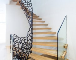 Floating wooden staircase with glass balustrade and a balustrade with metallic cell design, against a white wall.