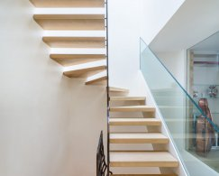 A staircase with wooden steps and a long glass balustrade on one side, and a metallic cell design on the other side.