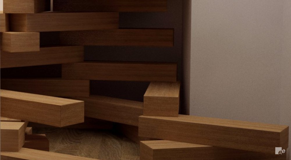 Wooden blocks, stacked up under a wooden staircase in front of a white stucco wall on a laminate floor.