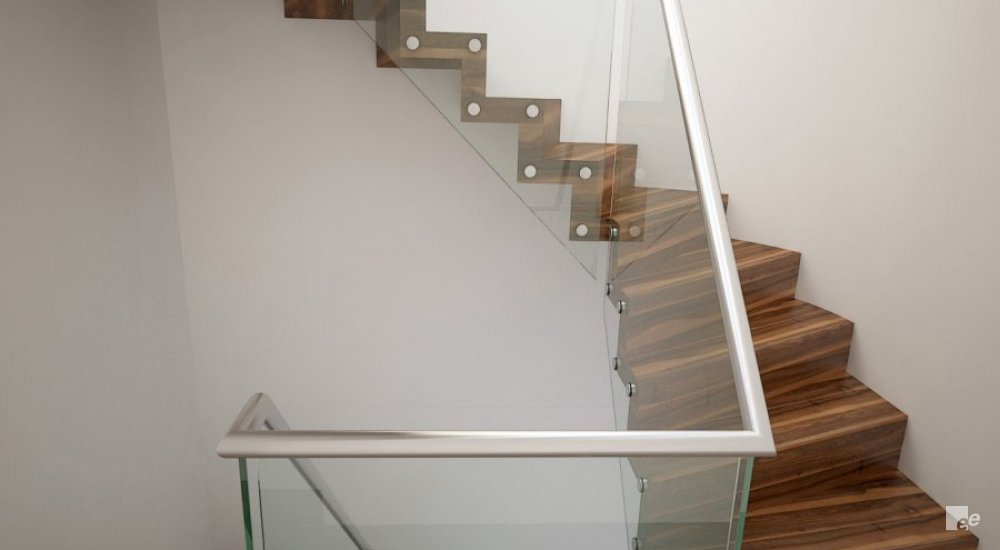 A floating staircase with dark walnut wood staircase treads, spacers and a balustrade in front of a white stucco wall.