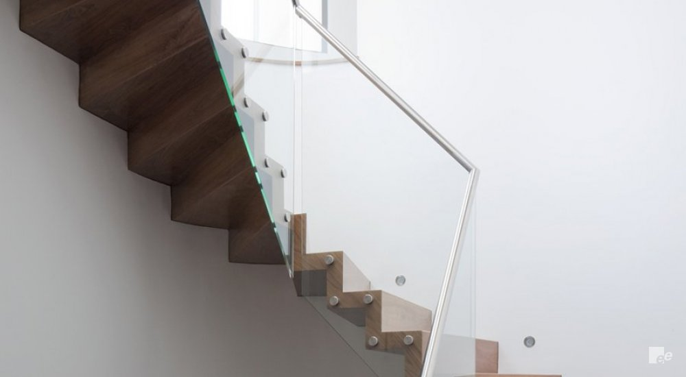 A window frame, wall lighting in a white stucco wall and a staircase with treads of dark walnut wood.